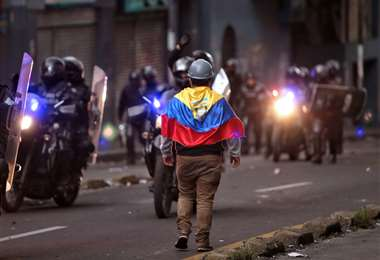 Un manifestante camina cerca de la policía antidisturbios durante los enfrentamientos en Quito. Foto AFP