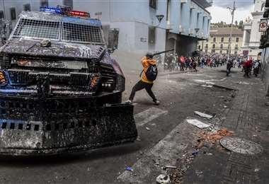 Un manifestante golpea un vehículo blindado con un palo durante los enfrentamientos con la policía antidisturbios en Quito. Foto AFP
