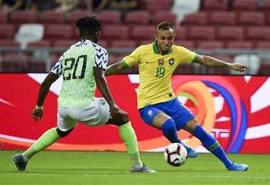 El brasileño Everton (19) intenta superar al nigeriano Chidozie (20) en el amistoso en Singapur. Foto. AFP