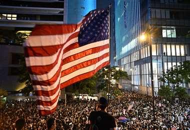 Un manifestante agita una bandera norteamericana durante la protesta. Foto: AFP