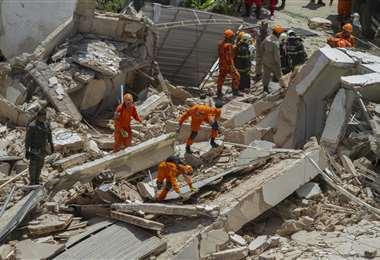 Los bomberos buscan sobrevivientes entre los escombros. Foto AFP