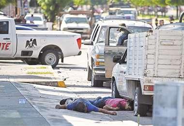 Dos cuerpos yacen en una calle de Culiacán donde se desató una batalla campal con los narcos. Foto: AFP