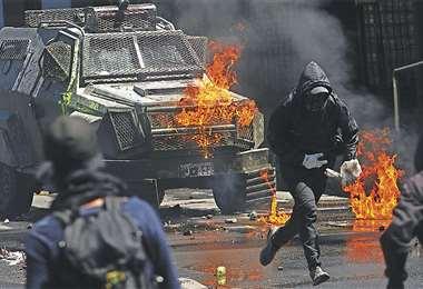Un manifestante radical usa una botella molotov para atacar a una tanqueta militar en Santiago. Foto: AFP