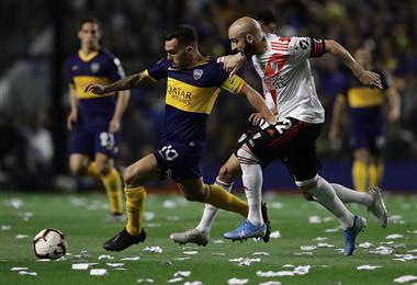 Tevez escapa a la marca de Pinola en la Bombonera. Foto. AFP