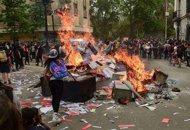 Los manifestantes queman documentos y objetos después de saquear una sucursal de un banco en Santiago. Foto AFP