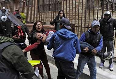 Una joven que participaba de la manifestación resultó desmayada por los gases. Fue retirada en brazos. Foto: AFP