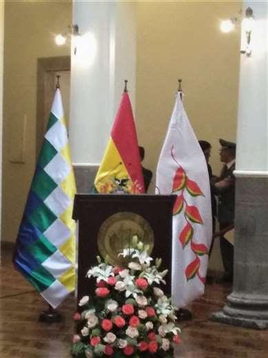 La bandera de la flor del Patujú a la derecha; en medio, la rojo, amarillo y verde; a la izquierda, la wiphala