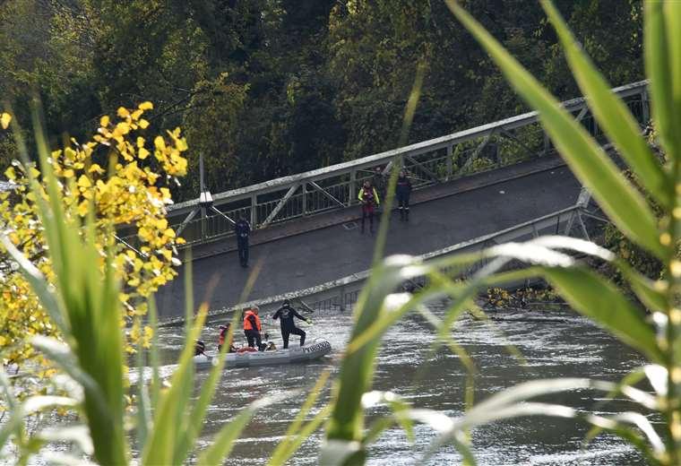 Rescatistas ayudan a las personas heridas en el puente. Foto AFP
