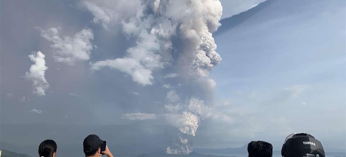 Turistas fotografían la enorme columna de humo del volcán Taal, cerca de Manila, capital de Filipinas. Foto: AFP