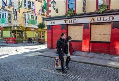 Dos personas caminan por una calle de Dublin. Foto AFP