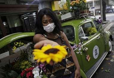 Roberta Machado ofreciendo sus flores. Foto AFP