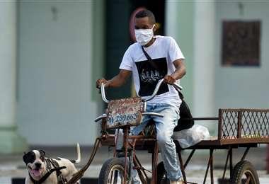 Un hombre con mascarilla en su triciclo por el centro de La Habana. Foto AFP