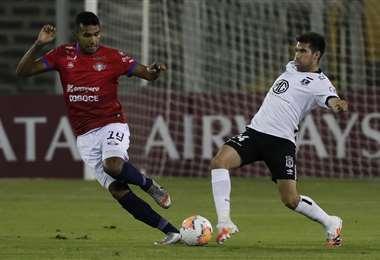 William Álvarez disputa la pelota con César Fuentes, de Colo Colo. Foto: AFP