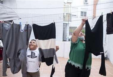 Andrei y Karen tendiendo la ropa en el patio interior de su casa. Foto El País