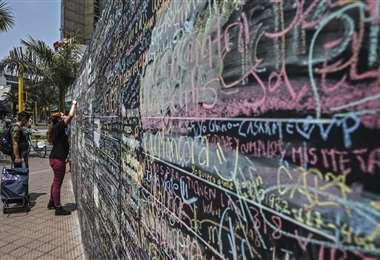 La gente escribe en el muro. Foto AFP