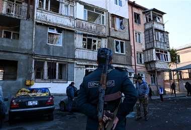 Un policía observa un edificio dañado por los bombardeos en Stepanekert. Foto AFP