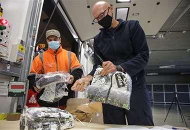Trabajadores del puerto de Amberes verifican mercancías. Foto AFP