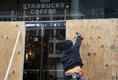 Un hombre protege con tablones un Starbucks en Washington. Foto AFP