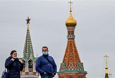 Dos personas con barbijos pasean por el centro de Moscú. Foto AFP