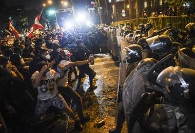 La policía trata de contener la marcha en Lima. Foto AFP