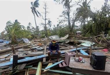 Un hombre sentado en lo que fue su vivienda. Foto AFP