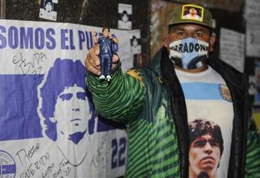 Un hincha sostiene una muñeco con la figura de Diego Maradona. Foto: AFP