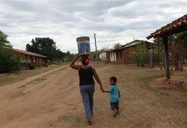 Antonia Chuvé Aguilar lleva agua agua en balde/Foto: Karina Segovia