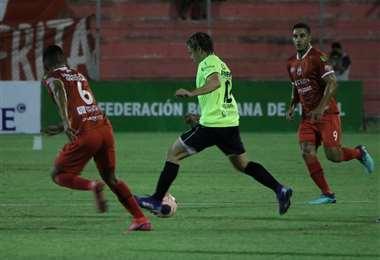 Aguirre maniobra entre Quiroga y Vogliotti. Foto: APG