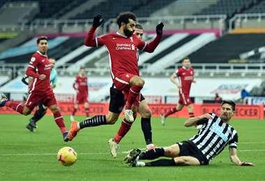 Salah salta ante dura entrada de un rival del Newcastle. Foto: AFP
