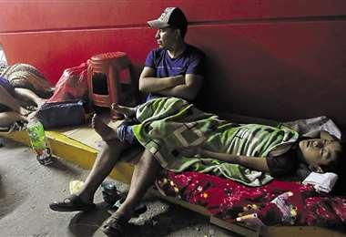 Este niño soporta los síntomas del dengue echado en el piso. Su padre espera el llamado del médico