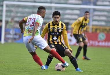 Thiago dos Santos, de Vinto, intenta sacarse la marca de Diego Wayar, del Tigre en el Hernando Siles. Foto. APG Noticias