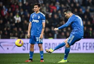 Cristiano Ronaldo remata ante la mirada de Dybala, su compañero en Juventus, que este sábado derrotó al colero del Calcio. Foto: AFP