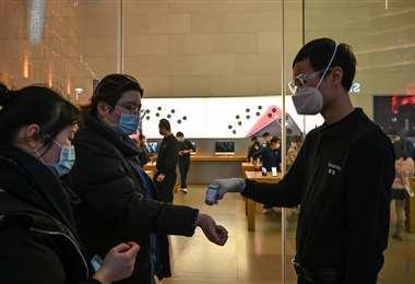 Un guardia de seguridad verifica la temperatura de los clientes en la entrada de una tienda de Apple en Shanghai el 25 de febrero de 2020 | Foto: AFP