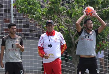 José 'Pepe' Peña (centro) observa a Mauricio Saucedo que intenta sacar un lateral durante una práctica de fútbol. Foto. Hernán Virgo