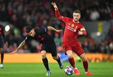 El delantero argentino del Atlético de Madrid, Ángel Correa, disputa el balón con el centrocampista inglés del Liverpool Jordan Henderson. Foto. AFP
