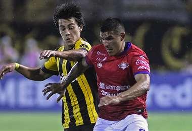 Cristian 'Pochi' Chávez, de Wilstermann intenta superar a Facundo Pellistri, de Peñarol. Foto. AFP