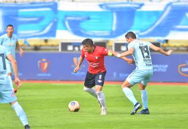 'Pochi' Chávez, de Wilstermann, protege el balón ante la marca de Óscar Ribera, de Bolívar. Foto. APG Noticias