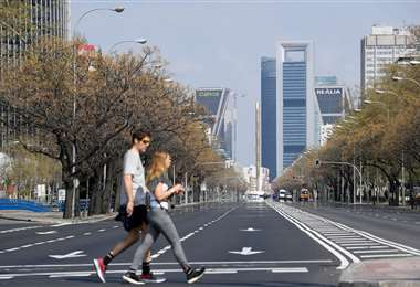 El 15 de marzo de 2020 dos personas cruzan la otrora ajetreada avenida La Castellana en Madrid, ahora vacía por el estado de alarma decretado por el gobierno debido al coronavirus que ya se ha cobrado 288 vidas en España  | Foto: AFP