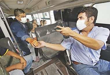 Este conductor de la línea 72 recibía con alcohol desinfectante a sus pasajeros. Ayer se comprobó que no todos lo hacen. Habrá control diario. Foto: Fuad Landívar