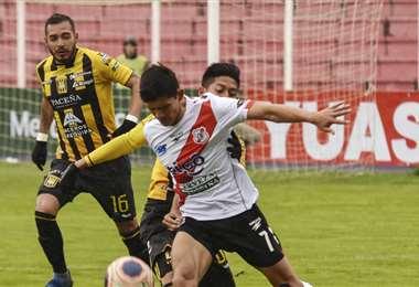 Edson Pérez, de Nacional domina el balón ante la marca de Ramiro Vaca, de The Strongest. Foto, APG Noticias