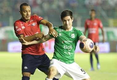 Marco Bueno, de Oriente protege el balón ante la marca de Ismael Benegas, de Wilstermann. Foto. Ricardo Montero