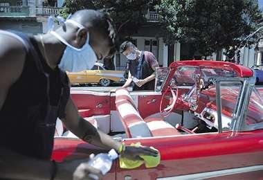 Dionis Díaz limpia su Chevrolet del 54, mientras espera turistas
