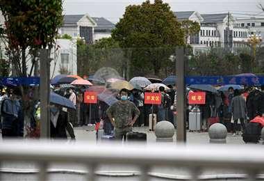 Las personas llevan máscaras faciales en la estación de trenes de Macheng en Hubei. Foto: AFP Foto: AFP