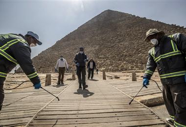 Los egipcios desinfectan las pirámides en la ciudad de Giza, próxima a El Cairo. Hay seis personas fallecidas y 41 casos positivos por coronavirus. Foto. AFP