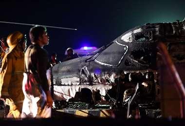 Los rescatistas se paran junto a los restos de un avión de Westwind, que se incendió durante el despegue en el aeropuerto internacional de Manila/Foto: AFP