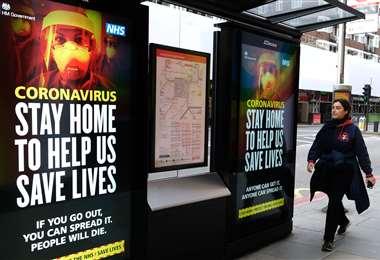 Una mujer cruza delante de carteles sobre el coronavirus en Londres, en una jornada de cierre nacional. Foto AFP