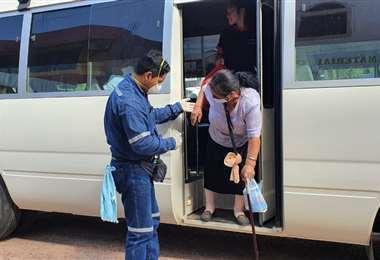 Un colaborador de Fuentes ayuda a una anciana a bajar del microbús. Foto: Fabricio Fuentes