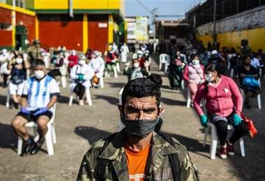 Empleados del mercado Ciudad de Dios de Lima esperan ser revisados para poder ingresar a trabajar. Foto AFP