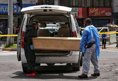 Personal de una funeraria de Quito (Ecuador, levanta un fallecido por causas desconocidas. Foto AFP