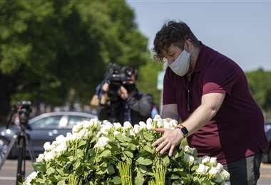 Un hombre amontona flores blancas en la Explanada Nacional de Washington en homenaje a los muertos por coronavirus. Foto AFP